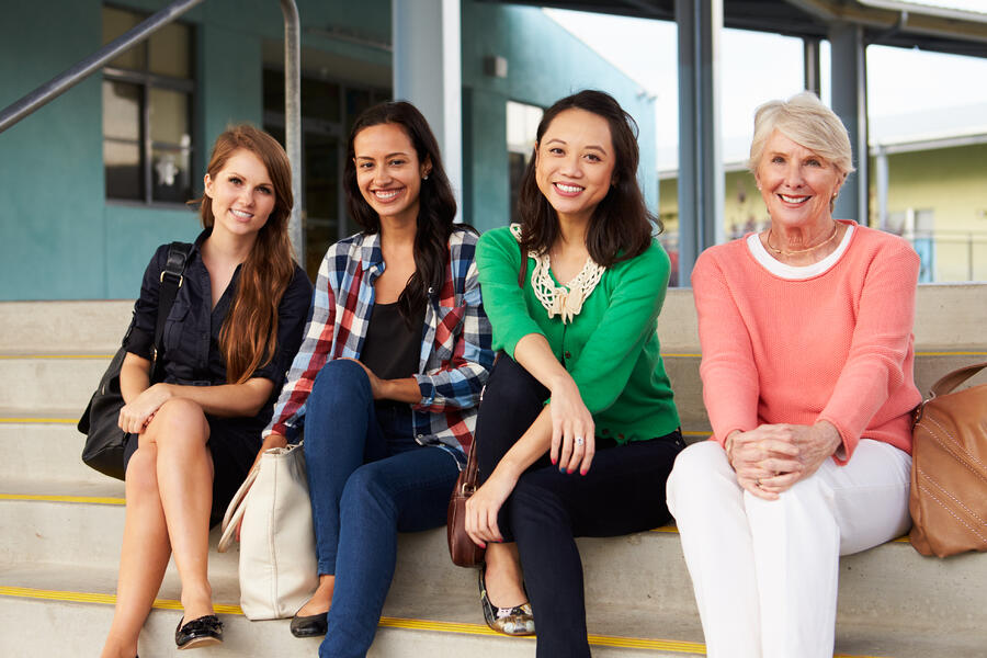 Four-female-teachers-sitting-on-steps-at-entrance-of-school-515264860_5086x3391 (1)
