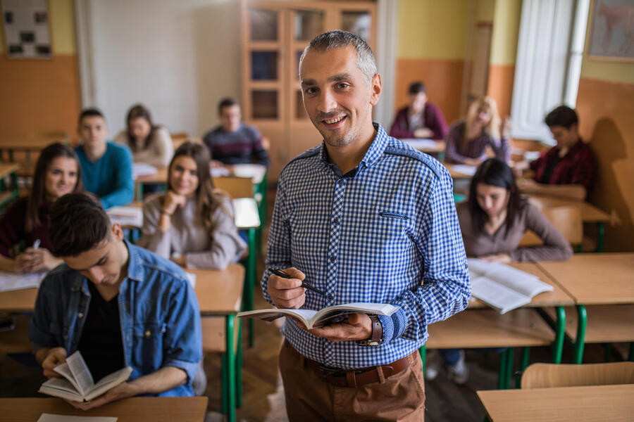 Happy-high-school-teacher-looking-at-camera-during-the-class-in-the-classroom.-859610548_6720x4480 (1)