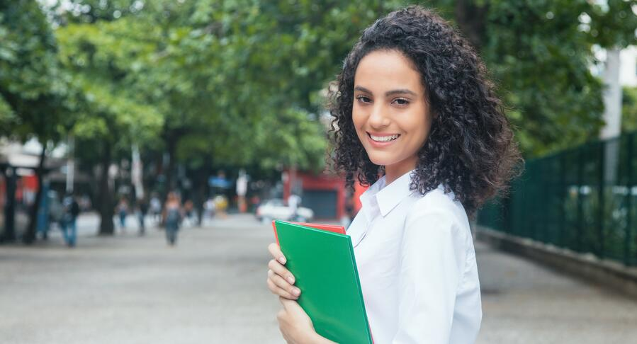 Happy-latin-female-student-with-curly-hair-and-white-shirt-845460816_7570x5475