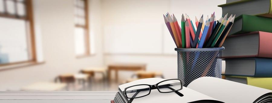School supplies on desk against empty classroom
