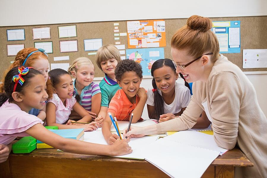 Teacher and pupils working at desk together at the elementary school-4
