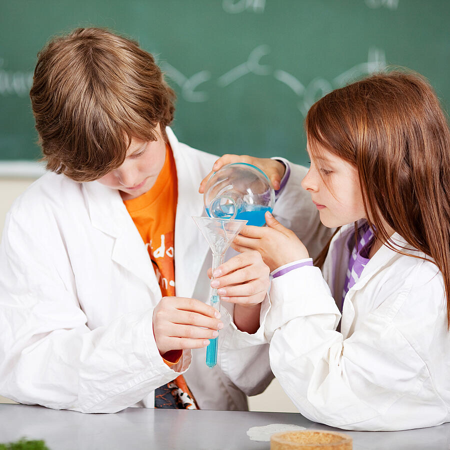 Young boy and girl in school learning chemistry working together as a team pouring liquids through a funnel into a test tube